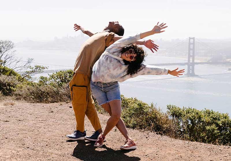 Man and woman posing outside by bridge, both wearing Tevas.