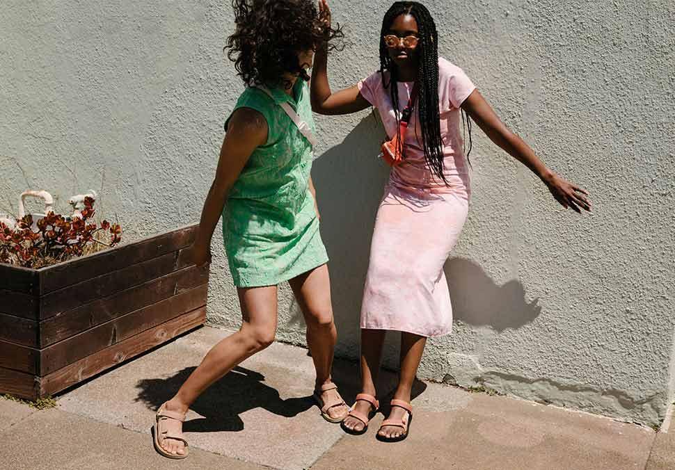 Two woman, wearing Teva Sandals, dancing on a sidewalk.