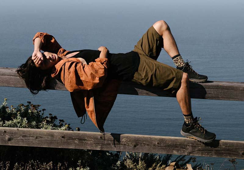 Man lying on a wooden handrail wearing the Grandview GTXs, with ocean behind him.