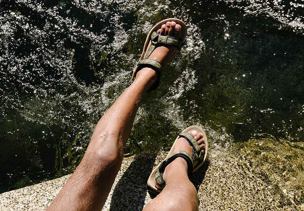 Close up of man's feet, wearing Teva Sandals, in the water.