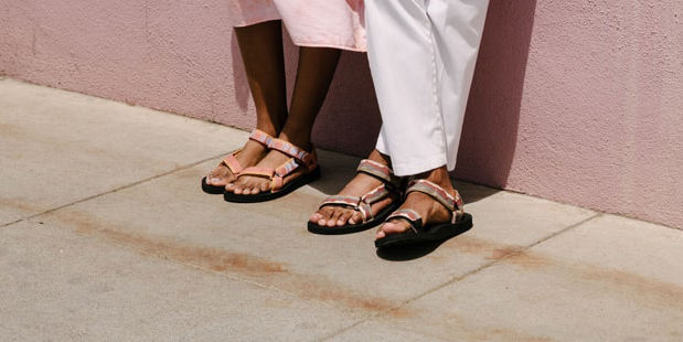 Close up of a woman and man's feet wearing Teva sandals.