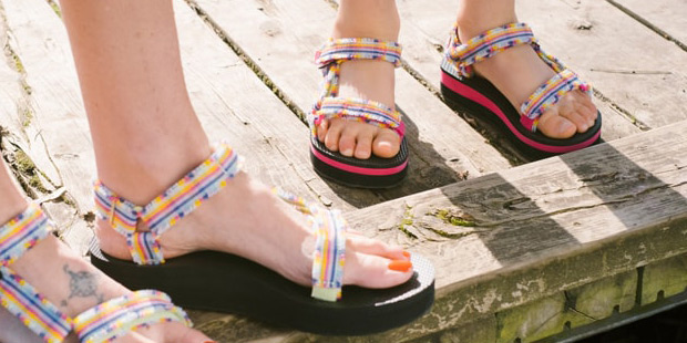 Close up of an adult and child's feet, wearing Teva Sandals, standing on a dock.