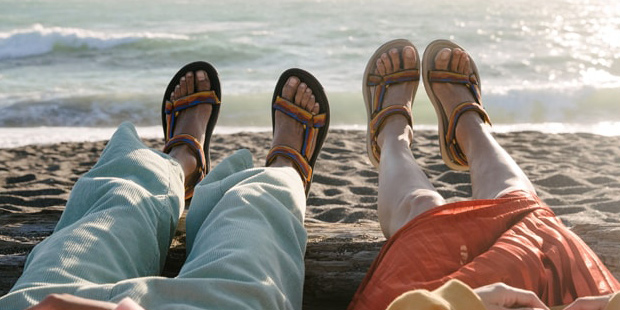 Close up of a woman and man's feet, laying on a beach, wearing Teva sandals.